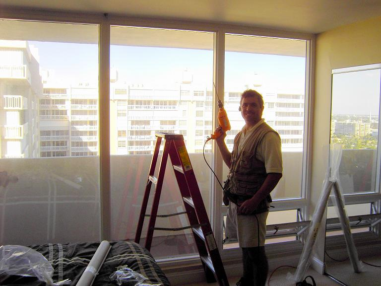 A picture of George preparing to install shades.